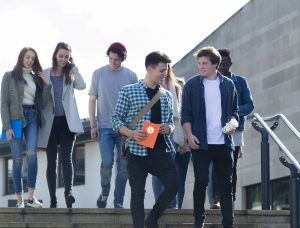 A group of students laugh and smile as they leave one of their lectures. They are walking down some steps carrying their books, bags and digital tablets.